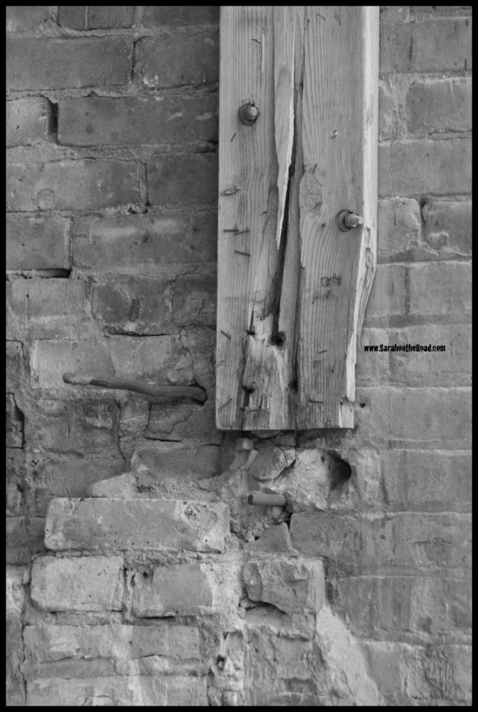 B&W shot of board bolted on side of brick building