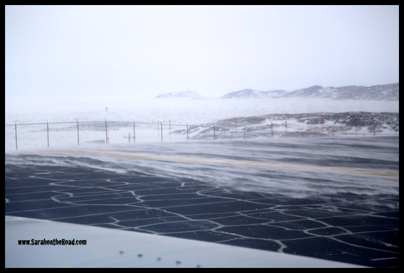Snow blowing across the ground on the runway